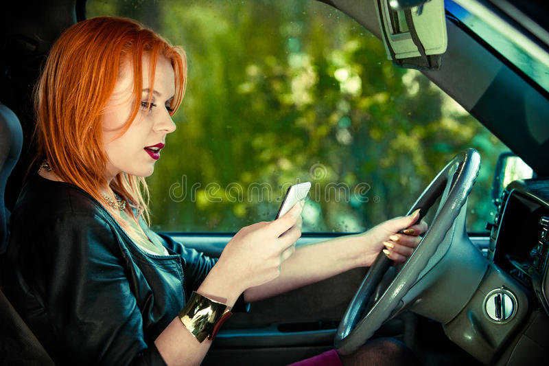 Woman driver sending text reading message on phone while driving stock photos