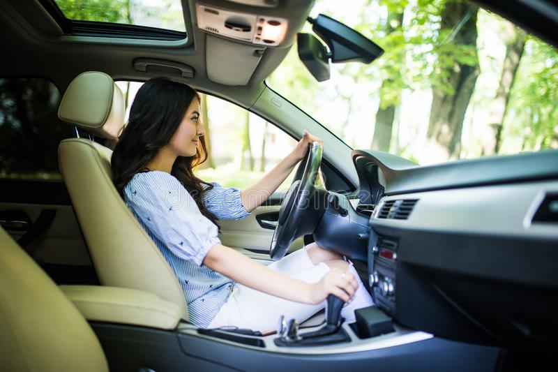 Woman driver shifting the gear stick and driving a car in the road royalty free stock photo