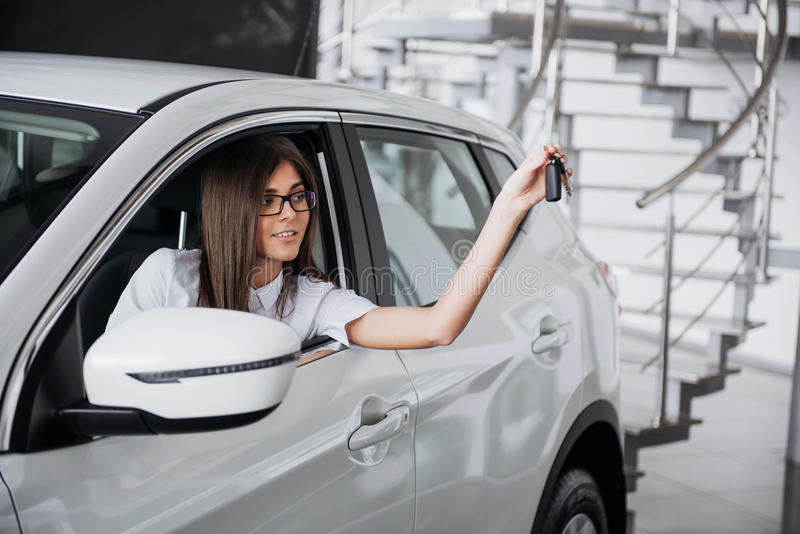 The woman driver smiling showing new car keys stock images