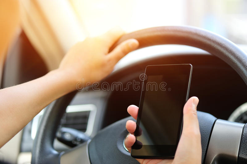 Woman driver use cell phone driving car royalty free stock photo