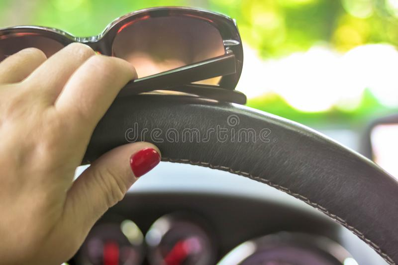 Woman driving a car with one hand holding the steering wheel and sunglasses stock photo
