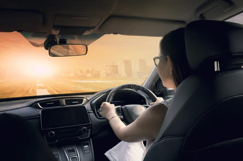 Woman driving car on urban highway against sun light and city bu royalty free stock image
