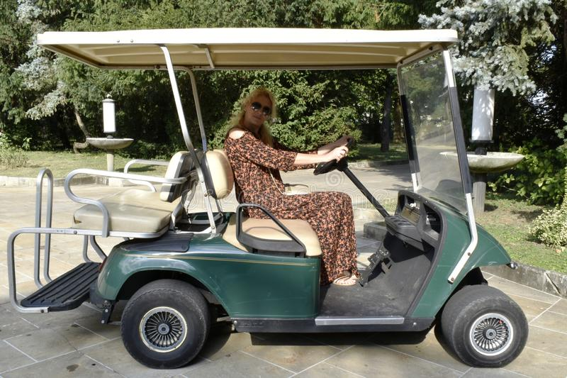 Woman driving golf carts stock photos