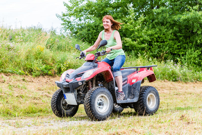 Woman driving off-road with quad bike. Or ATV royalty free stock image
