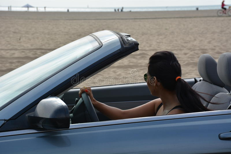 Woman driving by the side of the ocean beach stock images