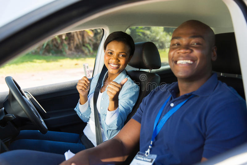 Woman driving test. African women has passed her driving test, holding driver's license stock photos