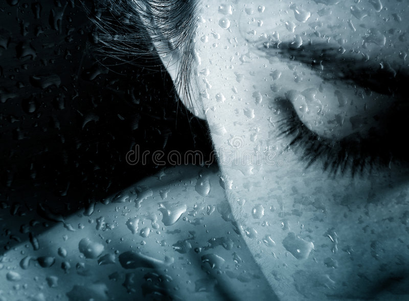 Woman and drops of rain. Picture a person young woman behind the glass with the drops of rain