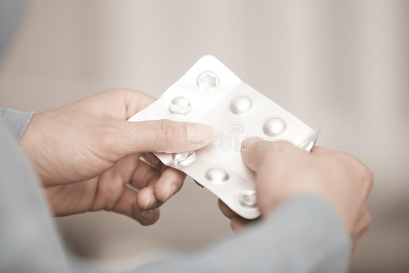 Woman with drugs. Hands of woman holding pack of medicament royalty free stock images