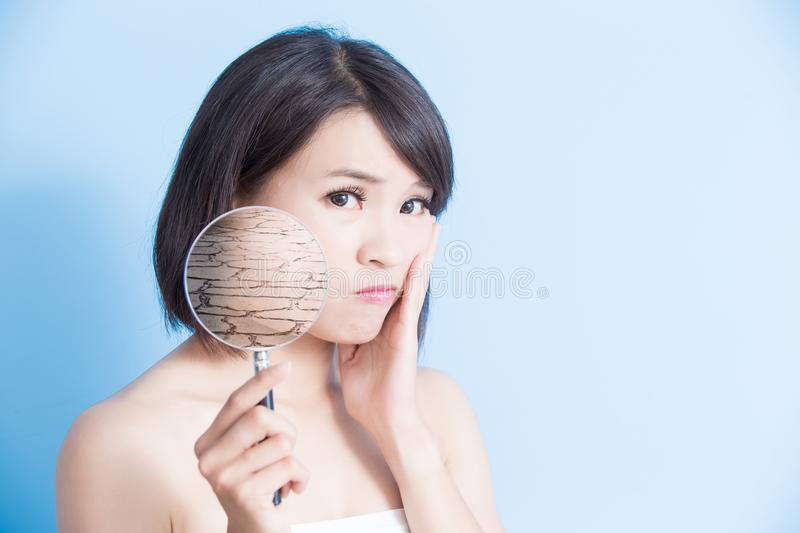 Woman with dry skin. Woman take magnifying with dry skin on the blue background royalty free stock photo