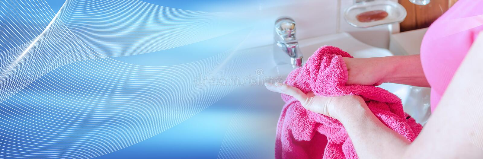 Woman drying her hands with a towel; panoramic banner. Woman drying her hands with a pink towel; panoramic banner royalty free stock photo