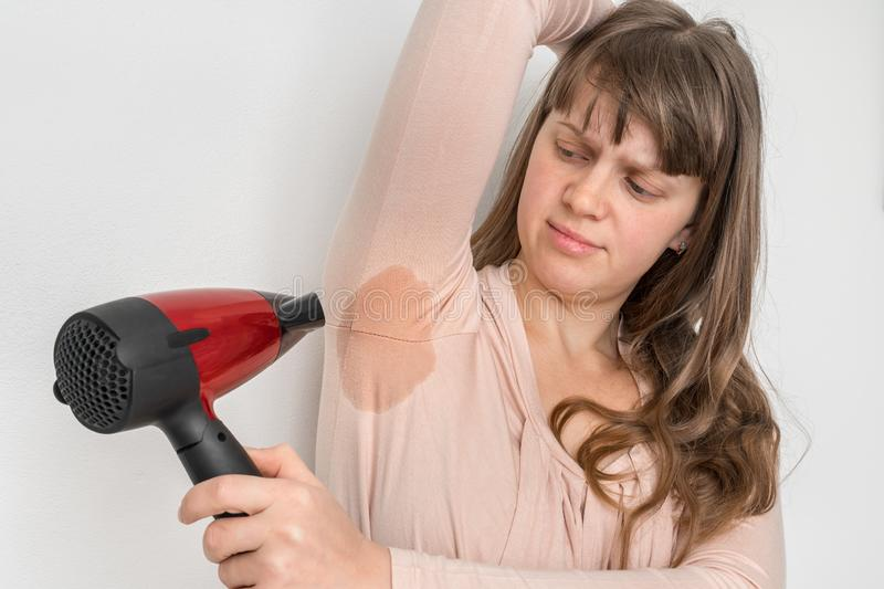 Woman is drying her sweating armpit with hair dryer royalty free stock photography