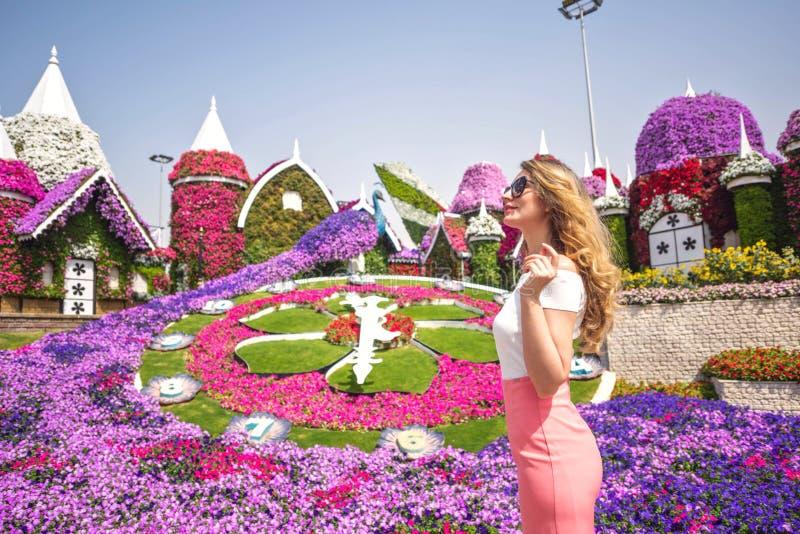 Woman in Dubai Garden portrait. Sunny day beautiful flowers backgrounds. Woman in Dubai Garden portrait. Sunny day beautiful flowers background stock photo