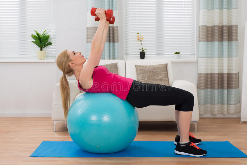 Woman With Dumbbell While Exercising On Fitness Ball stock photo