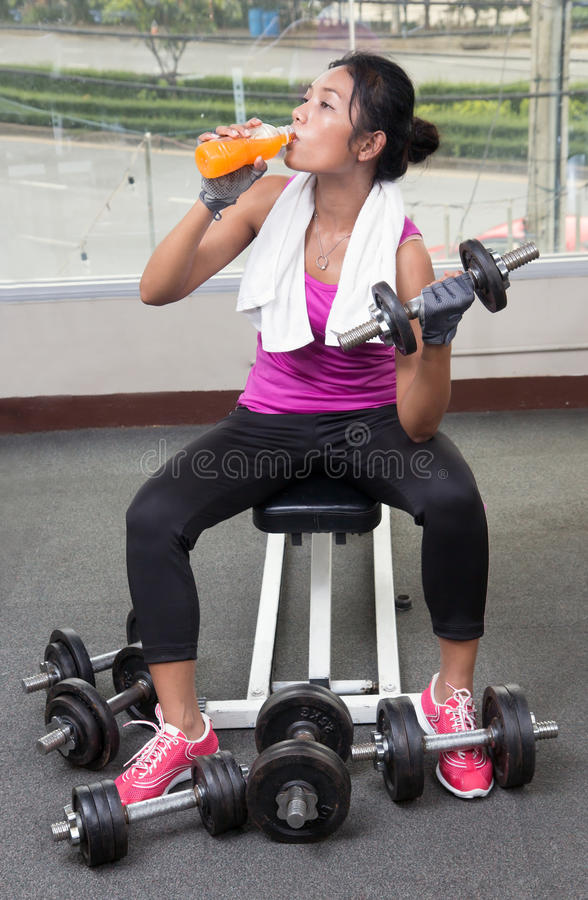 Woman with dumbbells drinking from a bottle royalty free stock images