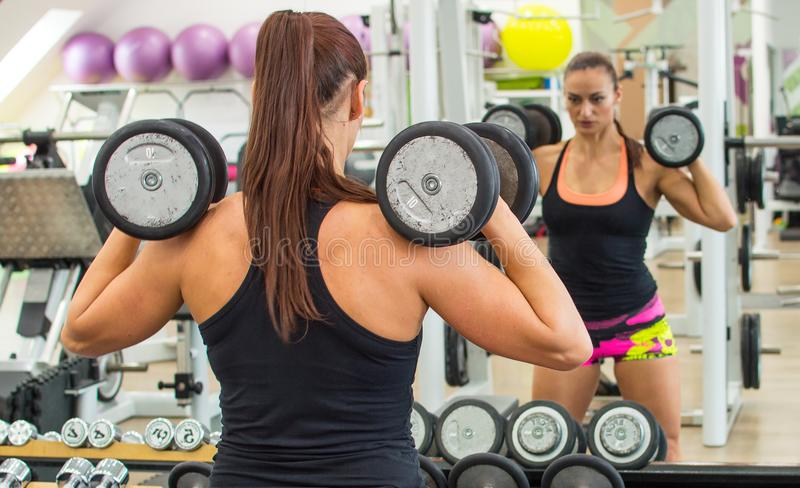 Woman with dumbbells. royalty free stock image