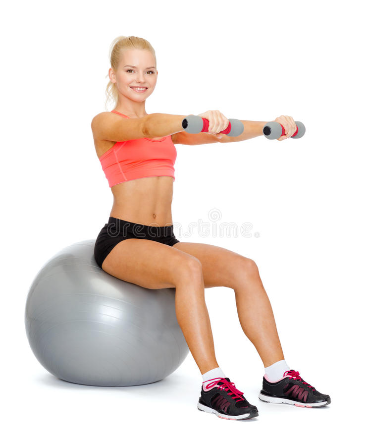 Woman with dumbbells sitting on fitness ball. Fitness, exercise and diet concept - smiling sporty woman with dumbbells sitting on fitness ball stock image