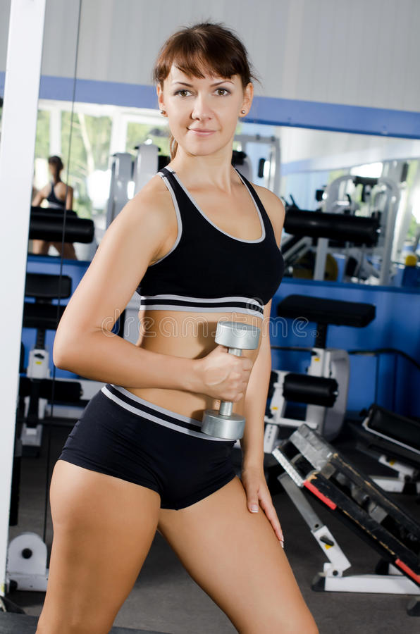 Woman with dumbbells in sports club. The caucasian woman with dumbbells in sports club royalty free stock photography
