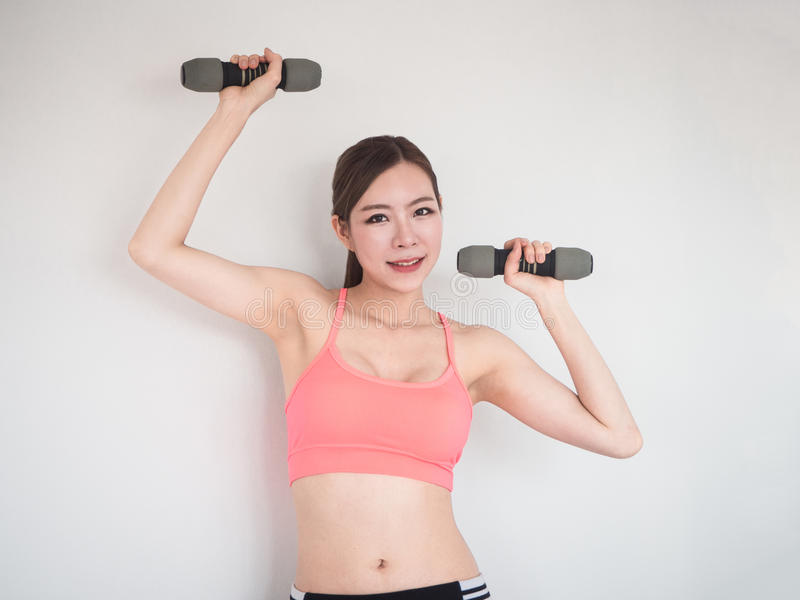 Woman with dumbbells working out on white background stock photo