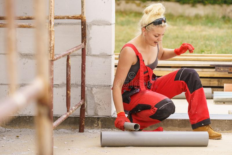 Woman installing pipes on construction site royalty free stock image