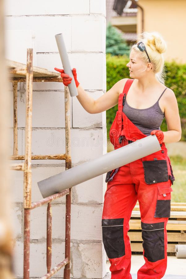 Woman installing pipes on construction site royalty free stock photography
