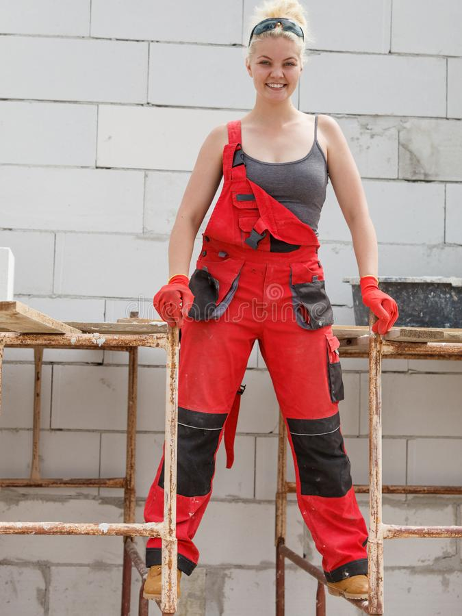 Woman in dungarees working on construction site stock photography