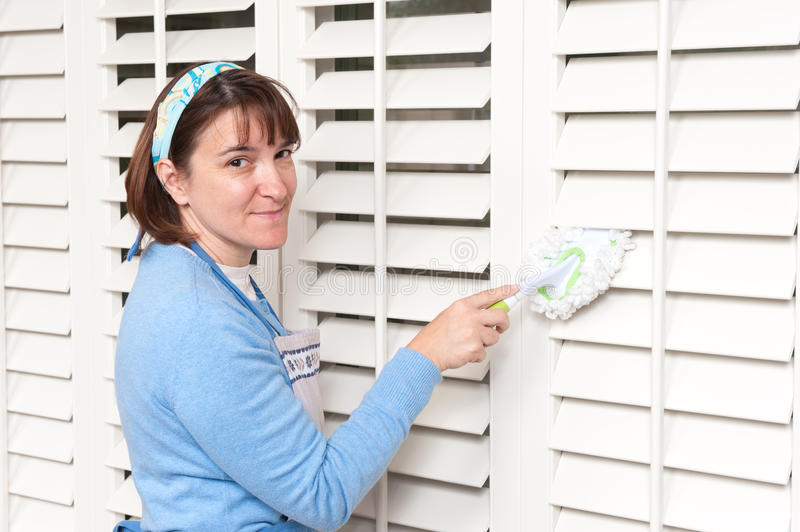 Woman dusting window shutters. A homemaker uses a hand held duster to clean some wooden window shutters stock photo