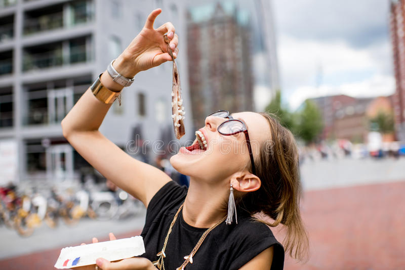 Woman with dutch herring. Young woman eating herring with onions traditional dutch snack near the Rotterdam market royalty free stock photography