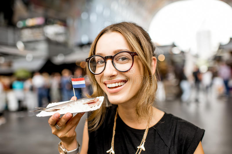 Woman with dutch herring. Young woman eating herring with onions traditional dutch snack in Rotterdam market stock photography