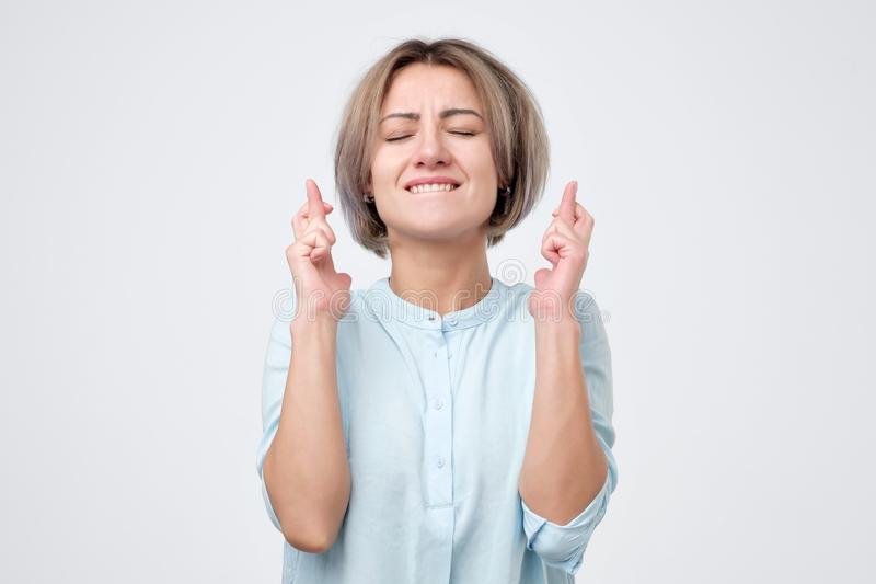 Woman eager to win competition, keeps fingers crossed as waits for results, poses in studio. stock photo