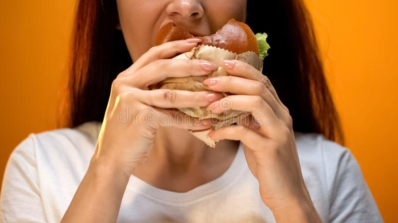 Woman eagerly eating tasty cheeseburger, bad eating habits, unhealthy snack stock images
