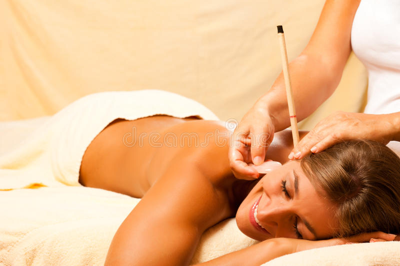 Woman with ear candles and gem massage royalty free stock photos