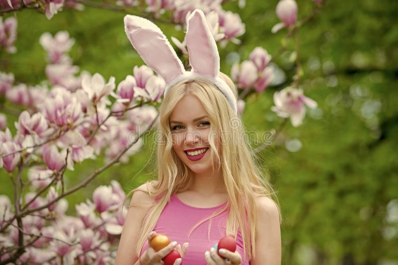 Woman with easter eggs on blossoming magnolia background stock image