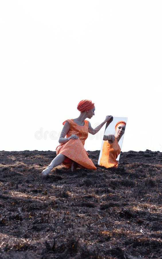 Woman in Eastern Clothes on Burnt Ground with Mirror royalty free stock photo