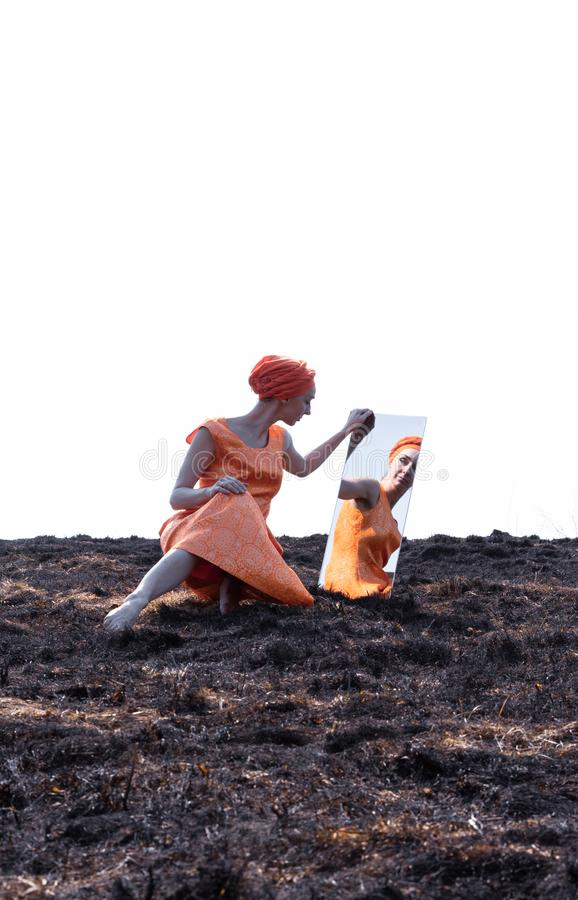 Woman in Eastern Clothes on Burnt Ground with Mirror stock photography
