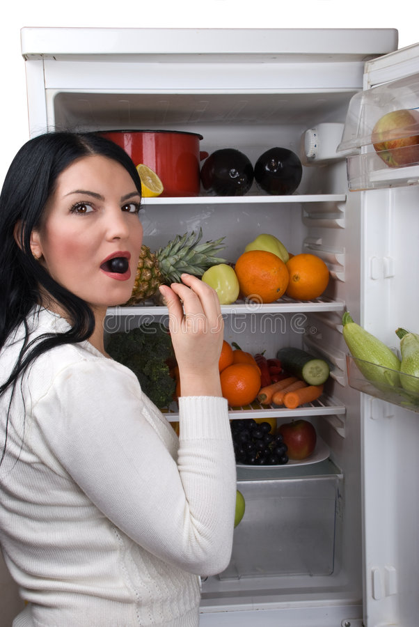 Woman eat a berry grape from fridge royalty free stock photography