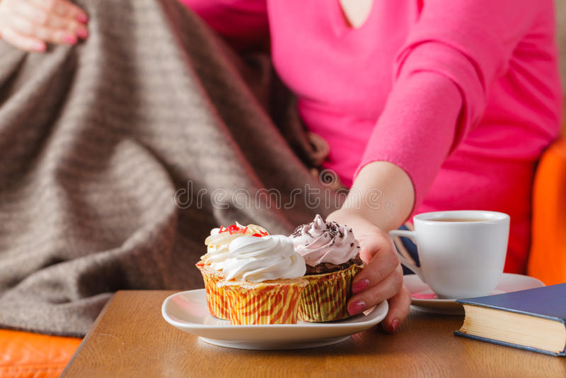 Woman eat cupcakes and drink tea royalty free stock photos