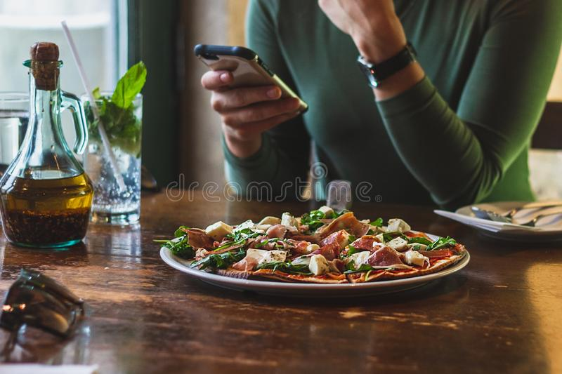 Woman eat pizza. Woman checks her phone while eat pizza royalty free stock image