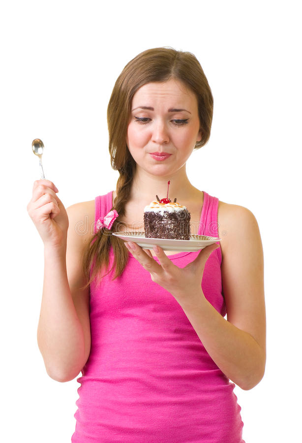 Woman eat tasty cake. The beautiful young woman eat tasty cake on white background royalty free stock photos