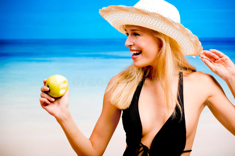 Woman eating apple. Woman with apple on the beach royalty free stock image