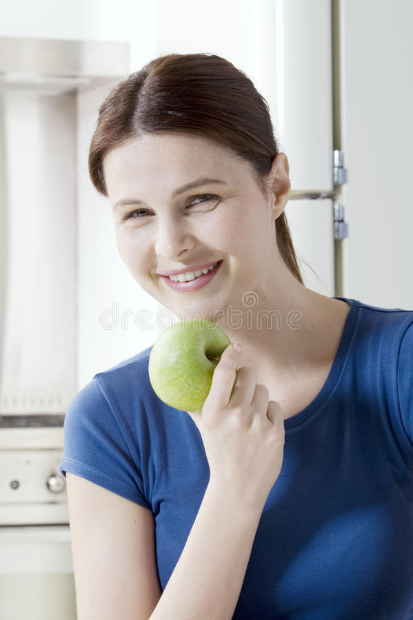 Woman eating an apple. In the kitchen stock photos