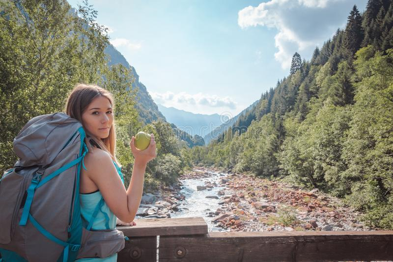 Woman eating an apple on a bridge surrounded by mountains royalty free stock image