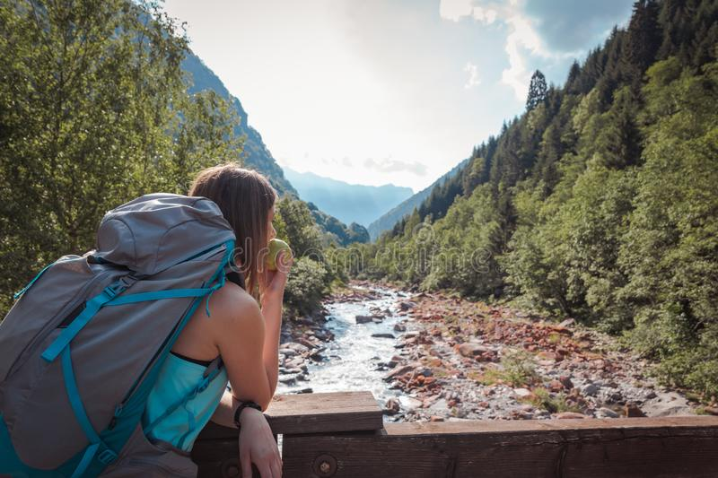 Woman eating an apple on a bridge surrounded by mountains royalty free stock photo