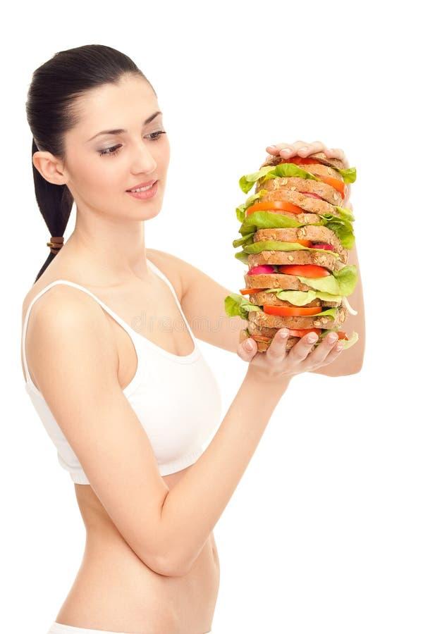 Woman eating a big sandwich royalty free stock photo