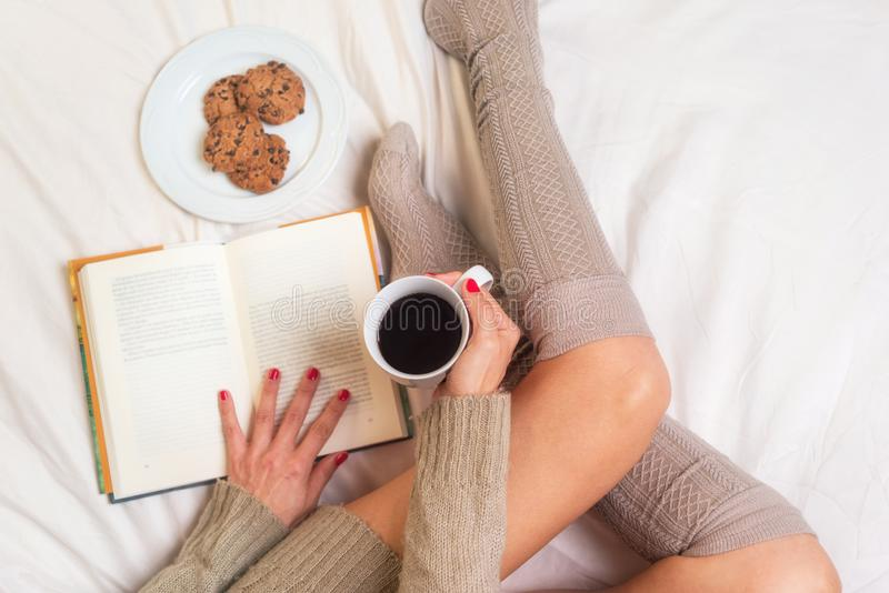 Woman eating breakfast in bed while reading a book royalty free stock image