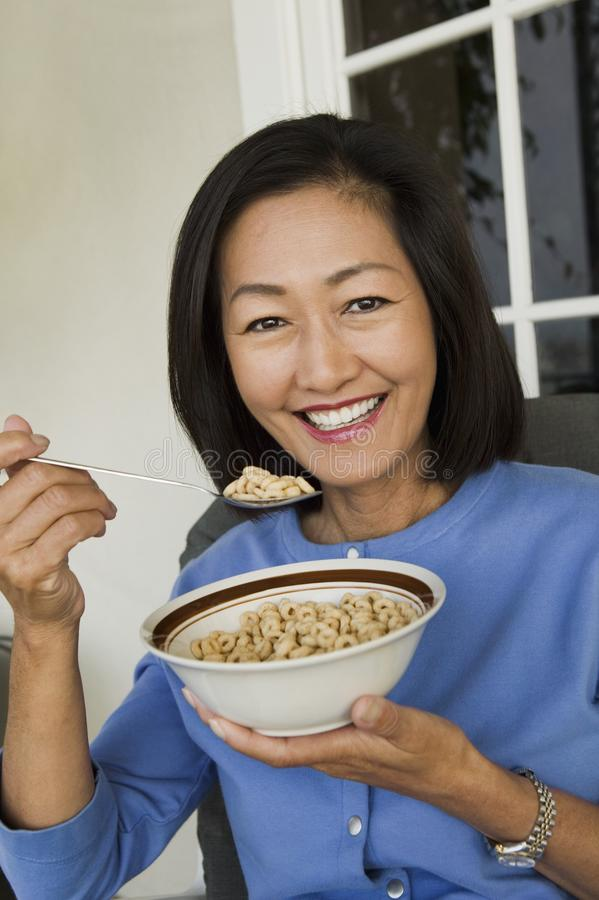 Woman eating breakfast cereal outdoors royalty free stock images