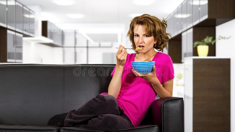 Woman Eating Breakfast on a Couch stock image