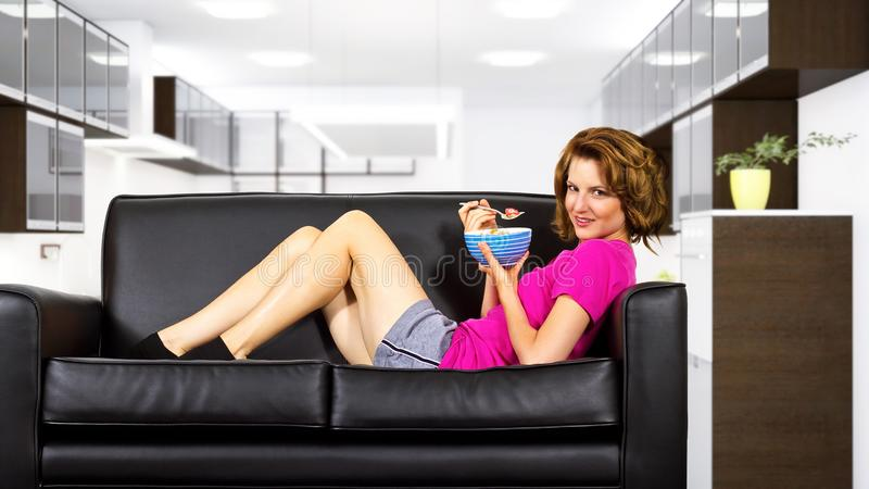 Woman Eating Breakfast on a Couch stock photo