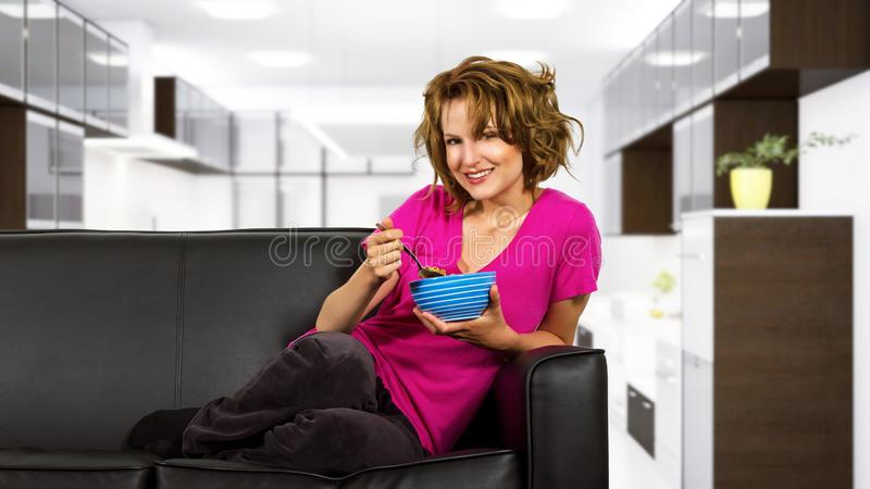Woman Eating Breakfast on a Couch royalty free stock photography