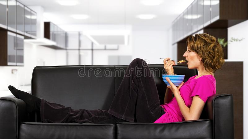 Woman Eating Breakfast on a Couch royalty free stock images