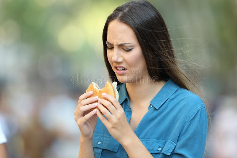 Woman eating a burger with bad taste. Disgusted woman eating a burger with bad taste on the street royalty free stock image